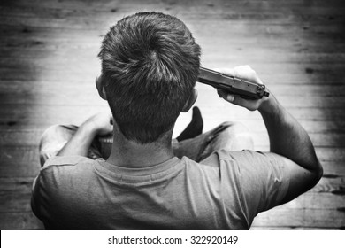 Man with pistol gun turned on his head wants to commit suicide, inside a house room. Black and white