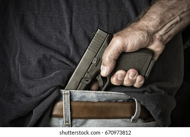 A man with a pistol in his waistband grasps the handle in preparation for pulling the weapon