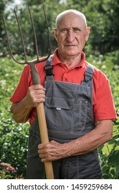 A man with a pitchfork standing on the farm, looking at the camera. Male farmer with a fork, standing in the open air.