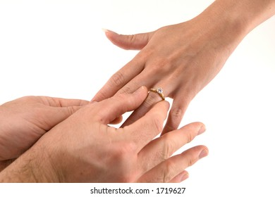 Man places engagement ring on his fiancee's hand after she accepts.