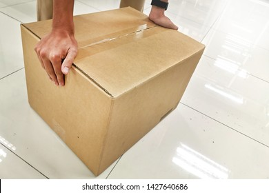 Man placing a big box on the floor