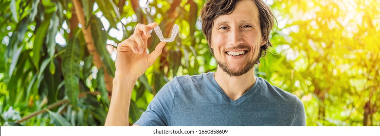 Man placing a bite plate in his mouth to protect his teeth at night from grinding caused by bruxism BANNER, LONG FORMAT