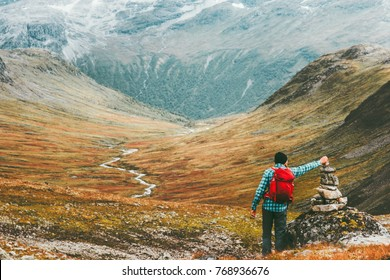 Man placing stone to rock cairn marking route hiking in mountains with backpack Travel healthy lifestyle concept active  vacations wild trek in Scandinavia