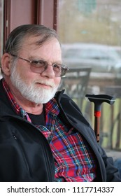 Man in plaid shirt and black jacket sitting on deck smiling but sad in eyes