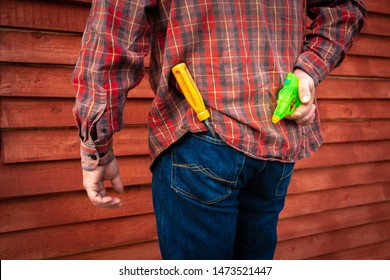A man in a plaid shirt hides a children's water gun behind his back. Screwdriver with a yellow handle sticking out of a pants pocket