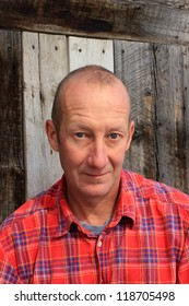 Man in plaid shirt with rustic background.
