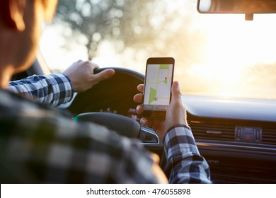 Man in plaid shirt sitting in the car and holding black mobile phone with map gps navigation, toned at sunset.