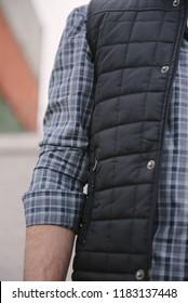 A man in a plaid shirt and waistcoat