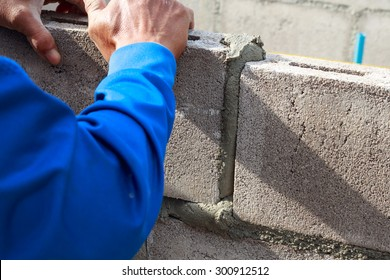 Man plastering and layering wall bricks in shallow depth of field.