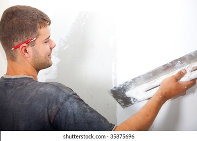 Man plastering the wall with a large spatula. At the corrosion imposed gypsum. Sharpness to face.
