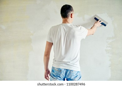 Man plastering the walls with finishing putty in the room with putty knife or spatula. Repair work, decoration building concept, construction.