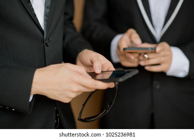 man play phone. finger touch screen smartphone. use phone. typing sms. play game. Two business man use smartphone
