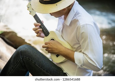 Man play ukulele near to the waterfall - people and music instrument life style in nature concept