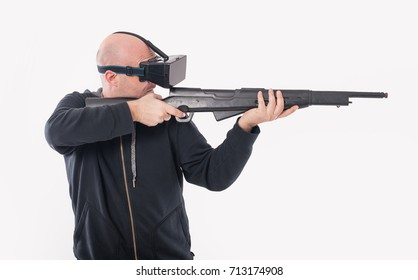 Man play VR shooter game with vr rifle and glasses. Studio shoot