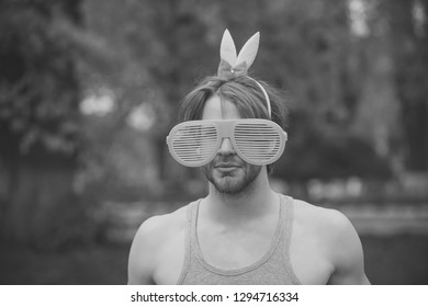 man, playboy, valentines day, easter., love games. sexy muscular man in glasses and pink ears on natural background. fashion and party celebration. spring and summer season.