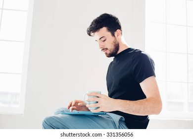 Man is played on the tablet. Student resting on campus