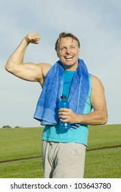 A man playfully flexing his muscles and laughing.