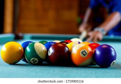 A man is playin billiard in a club