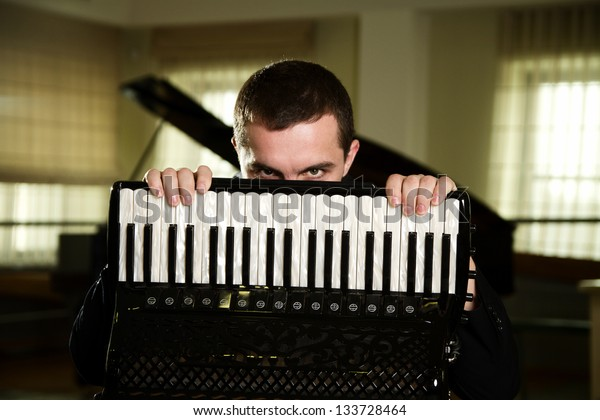 man playing the accordion in the hall