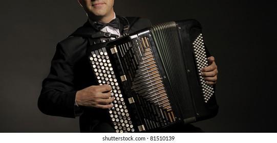 A man playing the accordion, studio shot.