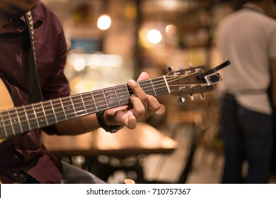 Man playing acoustic guitar in the bar at night shot with high iso with blur background