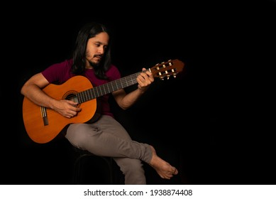 Man playing acoustic guitar with black background