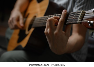 Man playing acoustic guitar, cover for online courses, learning at home.