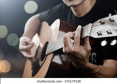 Man playing acoustic guitar with finger catching chord on bar on dark night light bokeh blur background