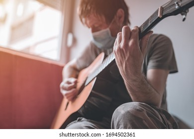Man playing acoustic guitar in home quarantine self-isolation during Covid-19 coronavirus outbreak