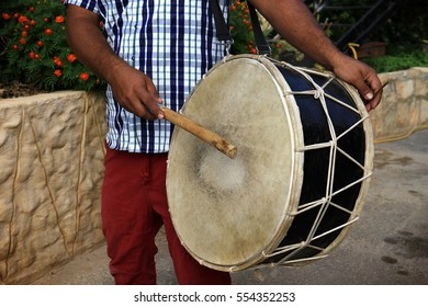A man playing an Arabic musical percussion instrument, tabl, used traditionally for Dabke dance.