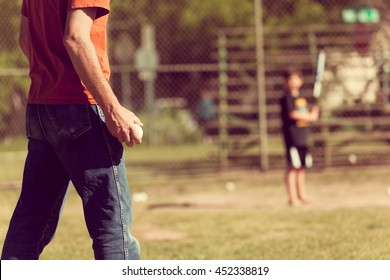 A man playing baseball with his son, vintage-toned