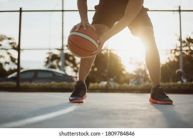 Hombre jugando al baloncesto. Hombre goteando un baloncesto al aire libre.