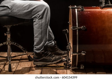 man playing the bass drum, wood Board with a black background, the concept of creative music, percussion instrument