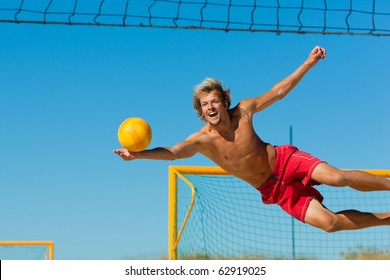 Man playing beach volleyball diving after the ball under a clear blue sky