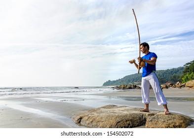 Man playing Capoiera Music Instrument, Berimbau