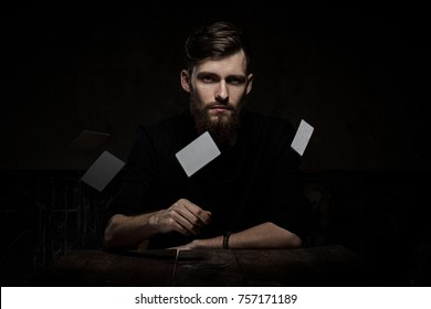 Man with playing cards on a dark background gambler