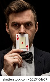 Man with playing cards in suit with bow tie
