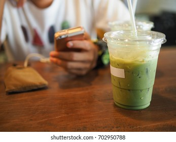 a man playing cell phone with green tea on the table