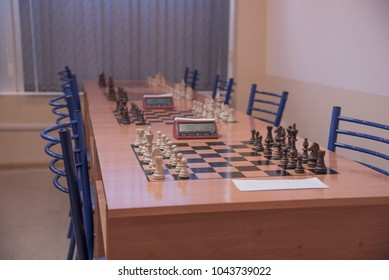 man playing chess. Chess club with tables. wooden chess board with wooden chess pieces. close up. black and white.