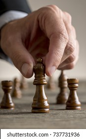 Man playing chess moving black queen piece in a close up view. Conceptual of business strategy planning.