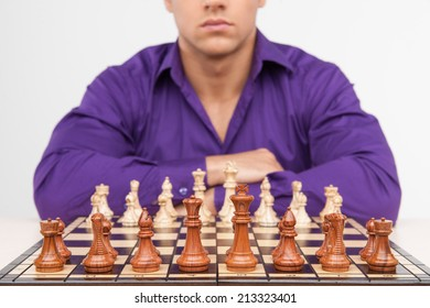 Man playing chess on white background. concentrated young man thinking about first move