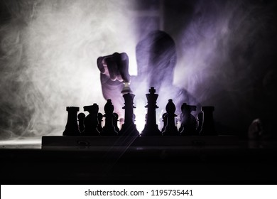 Man playing chess. Scary blurred silhouette of a person at the chessboard with chess figures. Dark toned foggy background. Selective focus. Horror concept