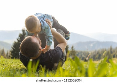man playing with child laying on green grass