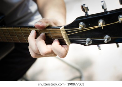 Man playing classic, acoustic guitar ,chord on an acoustic guitar