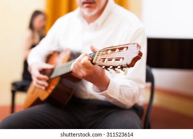 Man playing a classical guitar in a concert hall