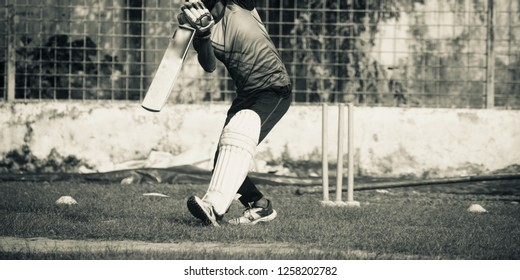 A man playing cricket wearing pads in a ground unique photo