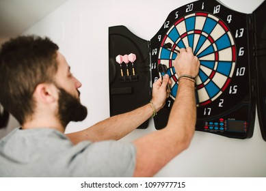 Man playing darts at home