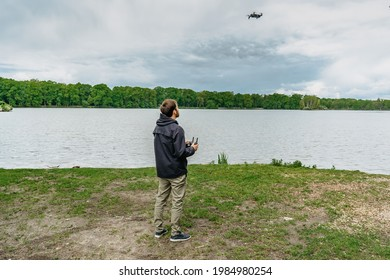 Man playing with drone for exam. Silhouette against fresh spring landscape.Male operating the drone by remote control and having fun. Pilot flying drone. Use of drone outdoors, piloting and media work