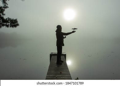 Man playing with the drone. Silhouette against the foggy landscape.Male operating the drone by remote control and having fun. Pilot flying drone. Use of drone outdoors, piloting and media work