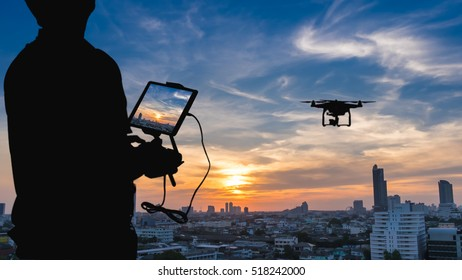 Man playing with the drone. Silhouette against the sunset sky over the city.